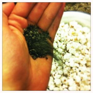 pouring green tea salt over popcorn