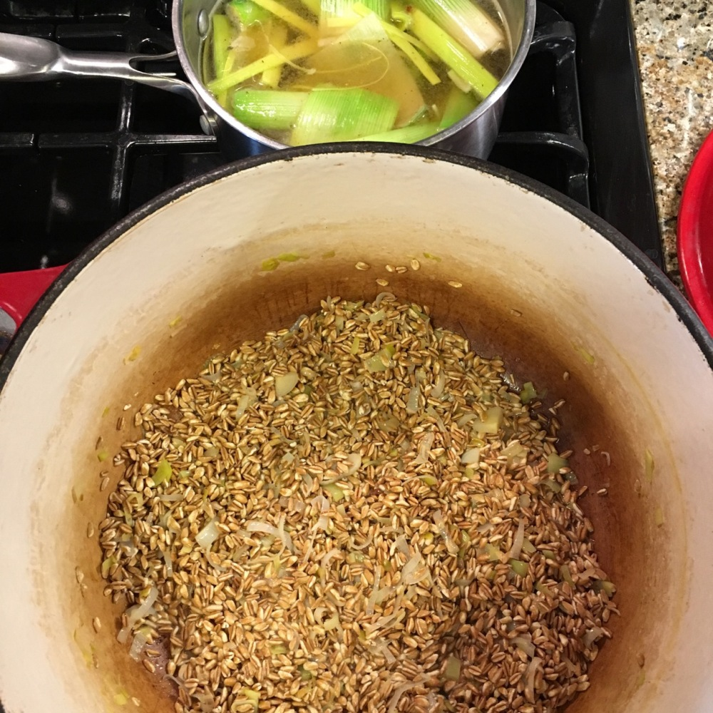 cooking farro risotto with leek infused broth
